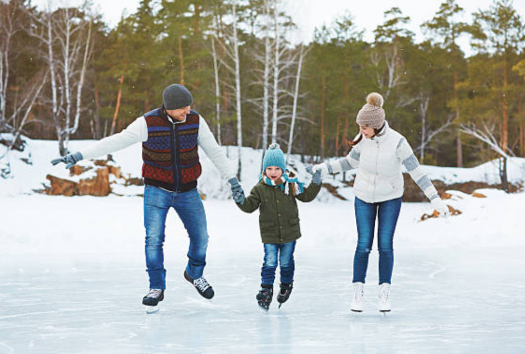 family skating on frozen lake